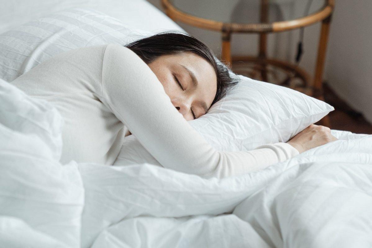 Woman Sleeping in White Bedding